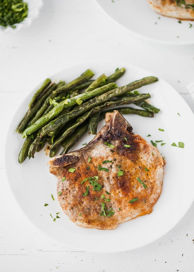 baked bone-in pork chops on a plate with green beans side